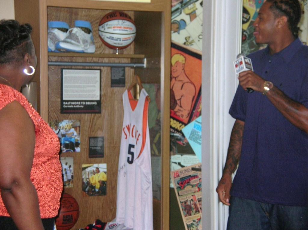 Last July, pre-gold medal Olympian, Melo had a special unveiling at Sports Legends Museum with some of his gear on display.  He's shown here with his Mom, seeming a bit surprised and delighted by the collection.